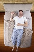 stock photo of deprivation  - top view of bedroom with insomniac man unable to sleep - JPG