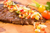 image of flank steak  - Whole flank steak served with corn salsa