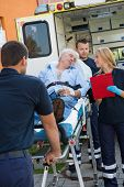 image of stretcher  - Paramedical team helping injured senior man lying on stretcher outdoors - JPG