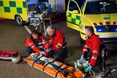 pic of stretcher  - Paramedics helping injured woman motorbike driver on stretcher at night - JPG