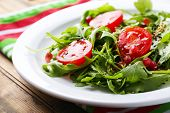 stock photo of sesame seed  - Green salad made with  arugula - JPG