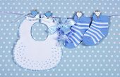 picture of teething baby  - Baby boy nursery blue socks and bib with dummy pacifier hanging from pegs on a line against a blue polka dot background for baby shower or newborn greeting card - JPG