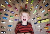 image of boys  - Boy lying on the floor with his car collection - JPG