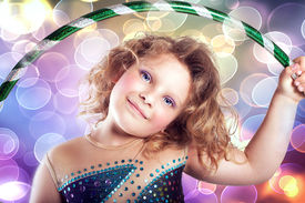 stock photo of hulahoop  - Portrait of pretty little girl with hulahoop looking at camera - JPG