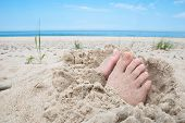 stock photo of toe nail  - Feet buried in sand with uncovered toes on a beach - JPG