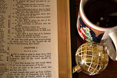 picture of bible story  - Bible opened to the Christmas story on a table top with an ornament and a holiday coffee cup - JPG