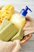 picture of bath sponge  - Greek olive soap with bath towels and bath sponge in basket closeup - JPG