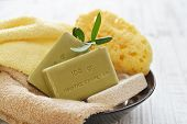 "stock photo of bath sponge  - Greek olive soap with bath towels and bath sponge in bowl closeup. The words on soap translates as ""best quality""