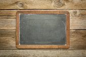 foto of slating  - blank slate blackboard against rustic weathered wood planks - JPG