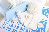 stock photo of menses  - Sanitary pads in box and sanitary pads and white flowers on blue calendar on light grey background - JPG