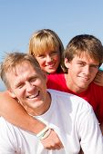 stock photo of family fun  - a happy young family posing together on the beach
