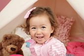 stock photo of teepee tent  - Happy toddler girl engaged in pretend play at home with a teepee tent - JPG