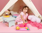 foto of teepee tent  - Happy toddler girl engaged in pretend play tea party indoors at home with a teepee tent