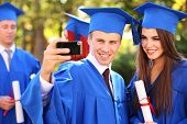 stock photo of graduation  - Graduate students wearing graduation hat and gown - JPG