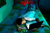 foto of boring  - Photo of a Young Teen sleeping in front of a laptop computer and on a bed - JPG