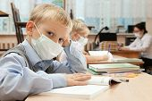 image of epidemic  - School children in medical face mask are learning in the half empty classroom during epidemic of flu - JPG