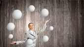 stock photo of juggling  - Young pretty businesswoman juggling with white balls - JPG