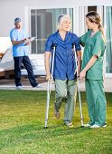 picture of crutch  - Female nurse helping senior woman to use crutches with caretaker in background at nursing home lawn - JPG