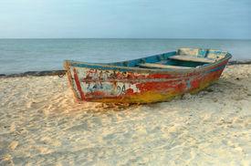 foto of sloop  - Solo rowboat with peeling paint resting on sandy beach in Progreso - JPG