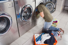 stock photo of laundromat  - Young man searching clothes inside washing machine drum at laundromat - JPG