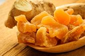 picture of home remedy  - Closeup dried candied crystallized ginger pieces and fresh root on wooden table - JPG