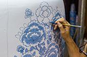 foto of handicrafts  - Hand with paintbrush painting a jar handicraft - JPG