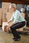 stock photo of pick up  - Warehouse manager picking up cardboard box in a large warehouse - JPG