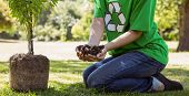 picture of planting trees  - Environmental activist about to plant tree on a sunny day - JPG