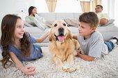 stock photo of cute dog  - Cute siblings stroking dog on rug while parents relaxing on sofa at home - JPG