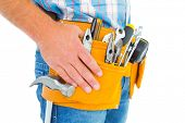 foto of handyman  - Midsection of handyman wearing tool belt on white background - JPG