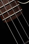 picture of fret  - Horizontal detail of the fret board of a bass guitar on a dark background - JPG