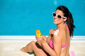 picture of suntanning  - Woman applying sunscreen or suntan lotion in her shoulder for solar skin protection at swimming pool - JPG