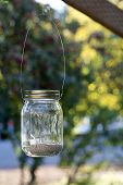 stock photo of mason  - mason jar with candle hanging on a tree as a decoration for wedding or party - JPG