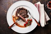 pic of ribeye steak  - Sliced medium rare grilled Beef steak Ribeye with grilled cherry tomatoes on white plate on wooden background - JPG