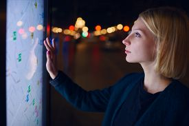 picture of touching  - Gorgeous young woman standing front big digital screen with basic city street map GPS data female touching sensitive display of modern smart city bus stop for check her location into the night - JPG