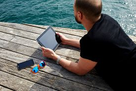 pic of jetties  - Tourist man using digital tablet while lying on wooden jetty at marina port during his vacation holidays - JPG