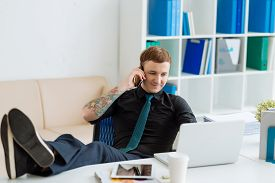 picture of table manners  - Modern businessman working at the office with his legs on the table - JPG
