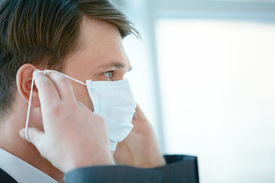 stock photo of face mask  - Portrait of businessman putting protective mask on his face - JPG