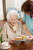 picture of meals wheels  - Senior Woman Being Served Meal By Carer - JPG