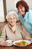 image of independent woman  - Senior Woman Being Served Meal By Carer - JPG