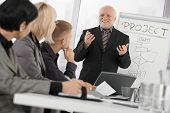 Senior businessman presenting on meeting to mid-adult coworkers, smiling, gesturing with both hands.