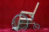 stock photo of antique wheelchair  - an antique wheelchair seen against red velvet - JPG