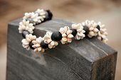 stock photo of kukui nut  - Kukui Nut Shell Lei on a grave stone - JPG