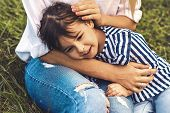 Cropped Closeup Image Of Happy Cute Little Girl Lying And Embrace On Her Mother Legs Outdoor. Loving poster