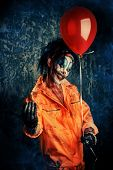 Sinister clown man stained in blood holding a balloon. Male zombie clown. Halloween. Horror. poster