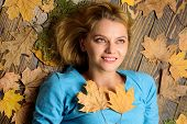 Girl Blonde Lay On Wooden Background With Orange Leaves Top View. Fall Atmosphere Attributes. Fall A poster