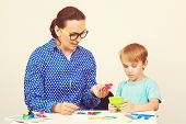 Teacher And Cute Little Boy Having Fun, Playing Logical Game. Kid With Teacher Learning At Preschool poster
