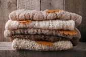 Background With Warm Sweaters. Pile Of Knitted Clothes With Autumn Leaves, Warm Background, Knitwear poster