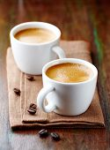 Two cups of espresso on rustic wooden table. Symbolic image. Coffee and coffee beans. Rustic wooden  poster