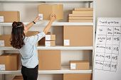 Office Worker Putting Parcel On The Shelf At Post Office poster